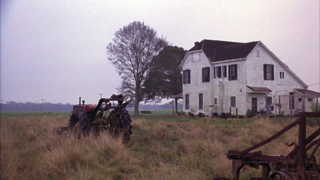WIDE ANGLE OF A WHITE TWO STORY FARMHOUSE, MAYBE FROM THE EARLY 1900S.  RUSTED FARM EQUIPMENT IN THE OVERGROWN FIELD.  A RED TRACTOR.  THE SKY IS GRAY, OVERCAST WITH WHITE FOG. FARMLANDS.
