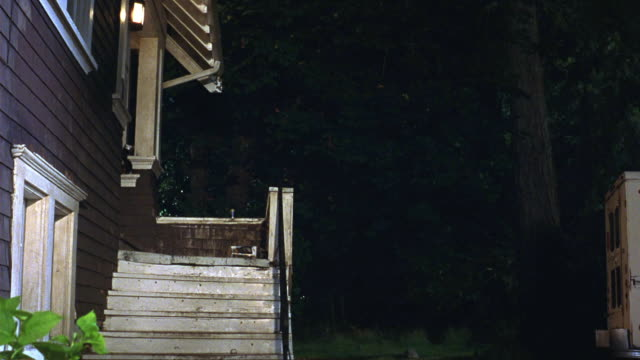 MEDIUM ANGLE OF STAIRCASE LEADING TO PORCH OR LANDING OF GRAY TWO STORY TUDOR STYLE HOUSE WITH WHITE TRIM. SEE PORCH LIGHT ILLUMINATED AT LEFT. SEE EDGE OF GRUMMAN DELIVERY TRUCK AT RIGHT. SEE DARKENED FOLIAGE IN BACKGROUND.