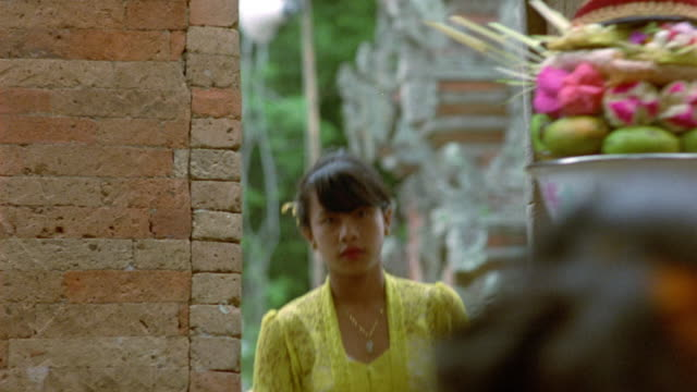 MEDIUM ANGLE OF YOUNG WOMAN WALKING THROUGH OPEN DOORWAY IN BRICK WALL, CARRYING BASKET OF FRUIT ON HER HEAD. SECOND WOMAN FOLLOWS. WOMEN WEARING YELLOW LACED TOPS. FOOD.