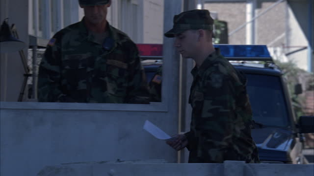 MEDIUM ANGLE OF THREE MILITARY PERSONNEL OR MEN OR SOLDIERS AT CHECKPOINT OR ENTRANCE GATE. PICKUP TRUCK WITH LIGHTS ON IT IN BACKGROUND. YOUNG MILITARY MAN GIVES PAPER TO MAN IN CA
