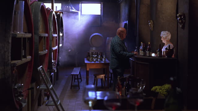 WIDE ANGLE OF ELDERLY MAN AND WOMAN TASTING WINE IN WINE CELLAR. GLASS BOTTLES AND WINE GLASSES SITTING ON WOOD BENCH AND STOOLS. MAN TURNS FROM BAR AND BEGINS TO WALK AWAY. COUPLES.