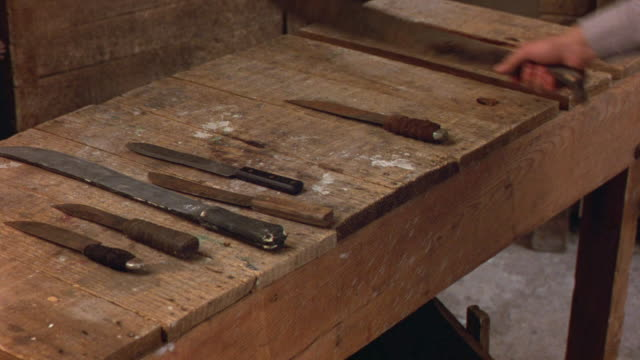 CLOSE ANGLE OF WOODEN TABLE WITH SEVERAL KNIVES ON IT. MEN WALK BY ONE BY ONE AND PICK UP KNIVES THEN CROSS IN FRONT OF CAMERA.