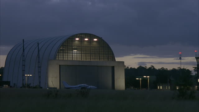 WIDE ANGLE OF HANGAR IN SMALL AIRPORT. SMALL AIRPLANE IN FRONT OF HANGAR. LIGHTS TURN ON IN TOP OF HANGAR. DARK GRAY SKY. FIELD IN FOREGROUND.