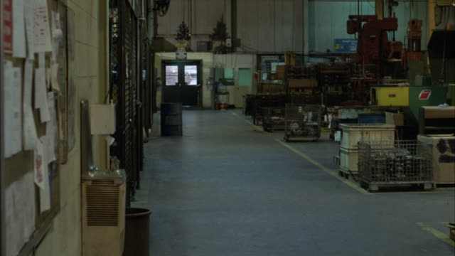 MEDIUM ANGLE OF EMPTY HALLWAY IN FACTORY. COULD BE MACHINE SHOP OR PLANT. SEE VARIOUS MACHINERY. MAINLY ALL MALE WORKERS BEGIN TO WALK OUT THROUGH HALLWAY. WORKERS WEARING WORK SHIRTS AND HARDHATS. SEEM VERY HAPPY AND EXCITED, PATTING EACH OTHER ON BACK.