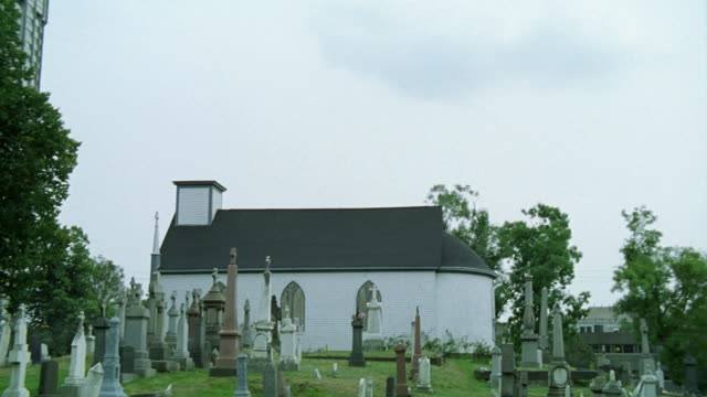 UP ANGLE OF CHURCH OR CHAPEL ON HILLTOP NEXT TO GRAVEYARD OR CEMETERY. HEADSTONES AND TOMBSTONES VISIBLE.