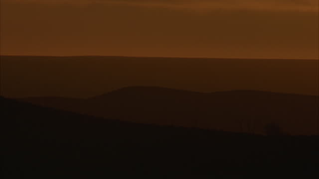 MEDIUM ANGLE OF BRIGHT ORANGE AND YELLOW SKY. SEE DARK ROLLING HILLS BELOW. PROBABLY DURING DESERT SUNSET.