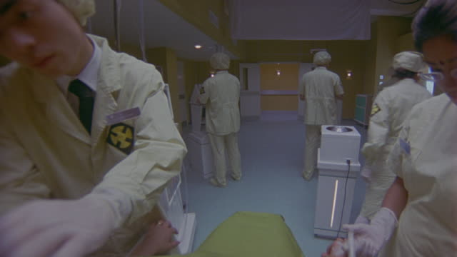 MEDIUM ANGLE OF SEVERAL WOMEN AND MEN IN SCRUBS, GLOVES, CAPS, AND OTHER MEDICAL GEAR WORKING IN FUTURISTIC HOSPITAL, EMERGENCY ROOM OR LABORATORY. COULD BE DOCTORS OR NURSES. COULD BE USED FOR SURGICAL PROCEDURE, MEDICAL EXAM, OR PATIENT POV.