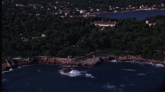 AERIAL OF RUGGED MEDITERRANEAN COASTLINE. BUILDING WITH SPANISH TILE ROOF, POSSIBLY RESORT OR HOTEL, SURROUNDED BY FOREST INLAND. COASTAL RESORT TOWN VISIBLE IN BG. NARROW ROAD BORDERS SEA IN FG. FRENCH RIVIERA.
