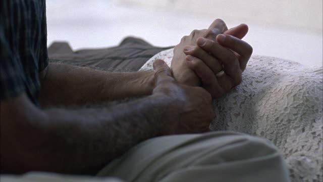 CLOSE ANGLE OF ARM OF ELDERLY WOMAN IN HOSPITAL BED. MEDICAL BRACELET. ELDERLY MAN HOLDS HER HAND. PAN UP TO THE MAN LOOKING AT THE PATIENT.