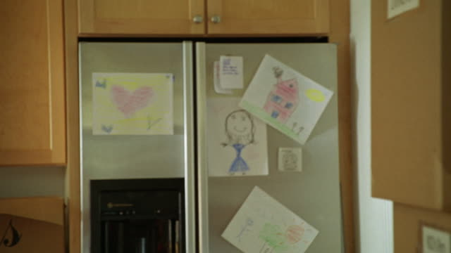 HAND HELD OF REFRIGERATOR IN KITCHEN OF MIDDLE CLASS OR SUBURBAN HOUSE OR HOME. CHILDREN OR KIDS DRAWINGS AND SKETCHES ON REFRIGERATOR DOORS.