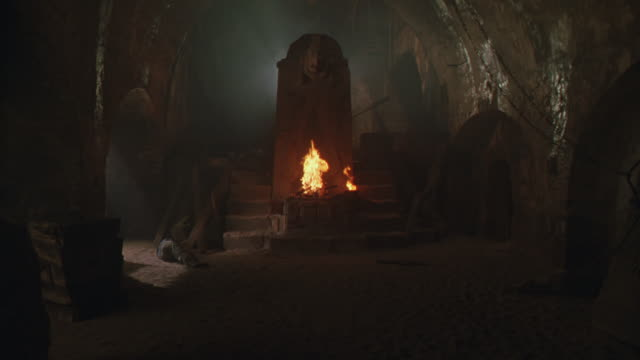WIDE ANGLE OF STONE BASEMENT CHAMBER WITH LARGE STONE IDOL OR ALTAR, CARVINGS. SMALL FIRE FLAMES BURNING AT BASE OF FIGURE.