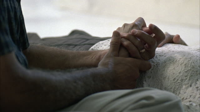 CLOSE ANGLE OF ARM OF ELDERLY WOMAN IN HOSPITAL BED. ELDERLY MAN HOLDS HER HAND. PAN UP TO THE MAN LOOKING AT THE PATIENT.