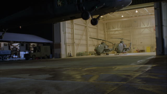 MEDIUM ANGLE OF HELICOPTER HANGAR AND TWO HELICOPTERS. A THIRD HELICOPTER ENTERS SCREEN FROM TOP AND LANDS, SEVERAL SOLDIERS EXIT AND RUN TOWARD CAMERA AND GET INTO TWO GREEN MILITARY JEEPS.
