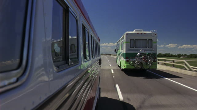 WIDE ANGLE FROM MOVING POV BESIDE RV OR MOTOR HOME DRIVING ON COUNTRY HIGHWAY OR FREEWAY. SEE ANOTHER RV DRIVING IN RIGHT LANE. POV PULLS UP NEXT TO RV. COUNTRYSIDE LANDSCAPE BEYOND SIDE OF ROAD. HILLY PASTURES OR PLAINS IN BACKGROUND.