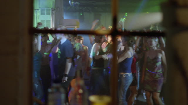 WIDE ANGLE OF DANCE PARTY OR RAVE PARTY THROUGH WINDOW. DANCERS ARE YOUNG ADULTS, COLLEGE AGED. TYPICAL DANCE FLOOR / CLUB SCENE WITH MULTI-COLORED LIGHTS PASSING BACK AND FORTH.