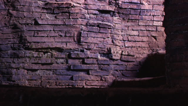 MEDIUM ANGLE OF A DARK BASEMENT OR LAIR OR DUNGEON. SEE DIRT FLOOR AND WORN BRICK WALL. STAIRS ON RIGHT. SEE LIGHT COMING FROM UPSTAIRS AND SHINING ON GROUND. SEE HUMAN SHADOW IN STAIRWELL.