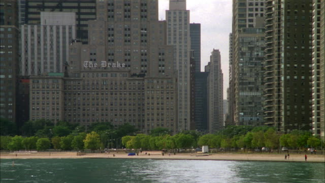 MEDIUM ANGLE OF DRAKE HOTEL AND LARGE APARTMENT BUILDINGS. SEE BEACH IN FOREGROUND WITH LAKE MICHIGAN. NEG CUT.