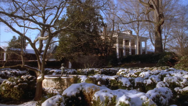 MEDIUM ANGLE ESTABLISHING SHOT OF MANSION WITH SNOW COVERED GARDEN IN FOREGROUND. HOUSE IS BRICK WITH LARGE WHITE IONIC COLUMNS IN FRONT. SEE BUSHES SURROUNDING SMALL FOUNTAIN WITH STATUE OF NAKED CHILD IN CENTER.