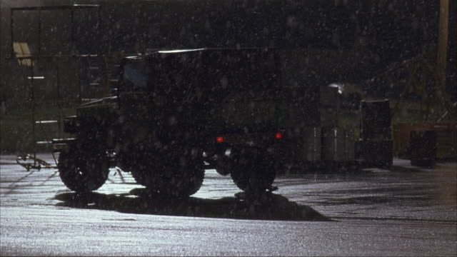 MEDIUM ANGLE ESTABLISH OF MILITARY VEHICLE OR JEEP FACING AWAY FROM POV. SEE CANISTERS STACKED NEXT TO JEEP. COULD BE IN INDUSTRIAL AREA OR MILITARY BASE OR CAMP. SEE SNOW FALL.