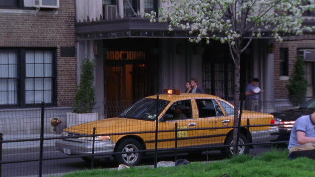 PAN UP PEDESTRIANS WALKING PAST AN UPPER CLASS OR MIDDLE CLASS APARTMENT BUILDING.  OTHER PEOPLE SIT IN A PARK IN FRONT OF THE BUILDING, MAYBE STUDENTS. COULD PLAY FOR A COLLEGE CAMPUS. A TAXI PARKED OUT FRONT.
