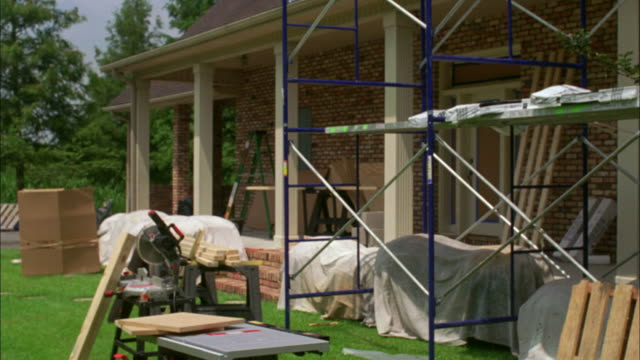 WIDE ANGLE OF MIDDLE CLASS HOUSE OR HOME WITH CONSTRUCTION SCAFFOLDS, SAWMILLS, AND CIRCULAR SAW AND LUMBER OUTSIDE.