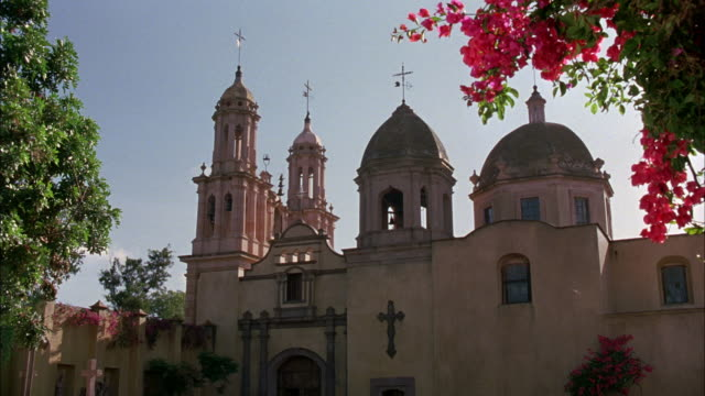 MEDIUM ANGLE OF EXTERIOR OF CATHOLIC CHURCH OR CATHEDRAL. SEE BEIGE STUCCO OR ADOBE WALLS OF BUILDING AND TWO DOMES ON TOP. SEE TWO TOWERS IN FRONT WITH CROSSES AT THE TOP.