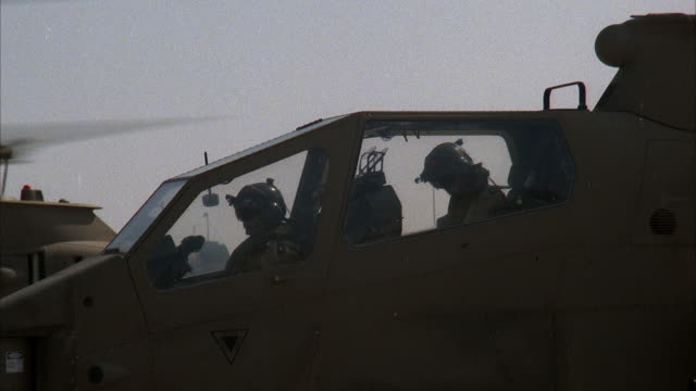CLOSE ANGLE OF FRONT OR COCKPIT OF COBRA MILITARY HELICOPTER WITH TWO PILOTS. PANS UP RIGHT TO HELICOPTER BLADE ROTATING, PANS BACK TO COCKPIT. MIDDLE EAST. ATTACK HELICOPTERS.