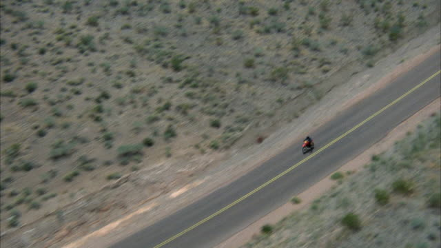 HIGH ANGLE DOWN TRACKING SHOT OF MOTORCYCLE OF DESERT HIGHWAY WITH SHRUBS ON SIDES. SOME CARS ON HIGHWAY. MIDDLE EAST.