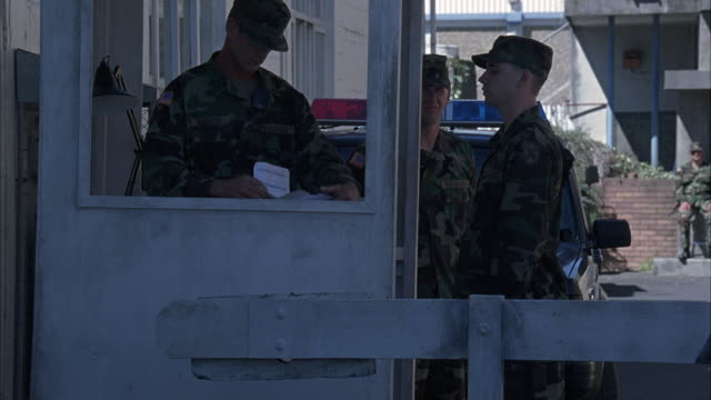 MEDIUM ANGLE OF THREE MILITARY PERSONNEL OR MEN OR SOLDIERS AT CHECKPOINT OR ENTRANCE GATE. PICKUP TRUCK WITH LIGHTS ON IT IN BACKGROUND.