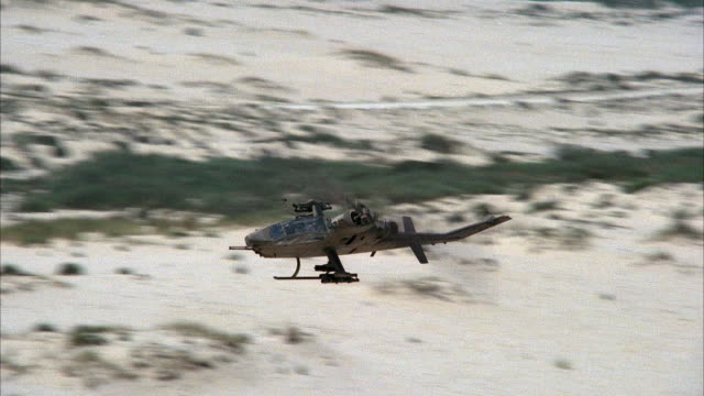 MEDIUM ANGLE TRACKING SHOT OF TWO COBRA MILITARY HELICOPTERS FLYING LOW TO GROUND. HELICOPTER FLIES BEHIND HILL AND REAPPEARS TO LEFT. HELICOPTER FACES FRONT. SAND AND BRUSHES IN BACKGROUND. MIDDLE EAST. ATTACK HELICOPTERS.