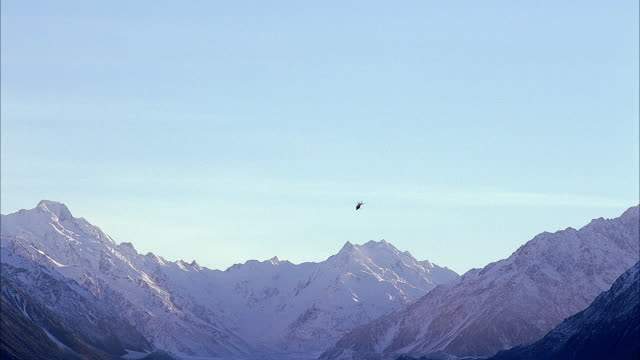 MEDIUM ANGLE OF SNOW COVERED MOUNTAIN TOPS OR SNOWY MOUNTAINS. SEE HELICOPTER FLY ACROSS TOPS OF MOUNTAINS. SEE CLEAR BLUE SKY IN BACKGROUND. COULD BE SOUTHERN ALPS OR ALASKA.