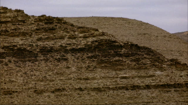 MEDIUM ANGLE OF SIDE OF DESERT MOUNTAINS. SEE SCATTERED PLANTS AND SHRUBS ON SIDE OF MOUNTAIN. SEE HAZY BLUE SKY IN BACKGROUND. COULD BE MIDDLE EAST, IRAN, IRAQ, OR NEVADA.