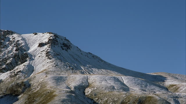 MEDIUM ANGLE OF SNOW COVERED MOUNTAIN. SEE ROCKS JUTTING OUT FROM SNOW. SEE BLUE SKY ABOVE. SEE ROUNDED PEAK OF MOUNTAIN.