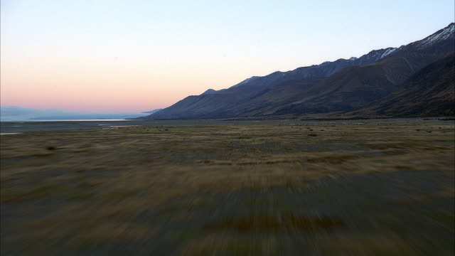 AERIAL OVER DIRT PLAINS. SEE YELLOWED GROWTH SPOTTING DIRT. SEE MIRROR-LIKE STREAMS CUT ACROSS LAND. SMOOTH SLOPES OF DARK BROWN MOUNTAINS ON RIGHT OF SCREEN. PINK BLUSH OF SUNSET BEHIND BLUE MOUNTAIN RANGES IN HORIZON.