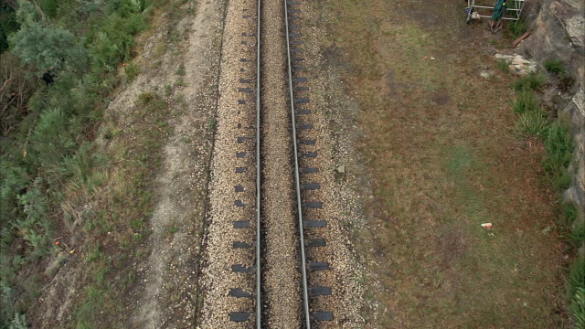 AERIAL OVER MOUNTAINSIDE RAILROAD TRACK. SEE GRAY ROCK WALL AT RIGHT AND DIRT COVERED SLOPE AT LEFT. SEE TRAIN MOVE UPWARDS ALONG TRACK.