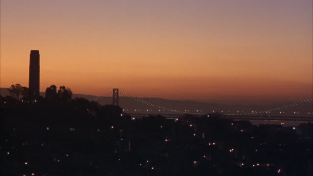WIDE ANGLE OF GOLDEN GATE BRIDGE AND MOUNTAINS IN FAR BACKGROUND. SEE COIT TOWER TO LEFT AND TELEGRAPH HILL IN FOREGROUND. SKY HAS TINT OF ORANGE. BEAUTY SHOT.