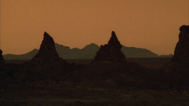 WIDE ANGLE OF TWO CONE SHAPED ROCK FORMATIONS EXTENDING UP FROM DESERT FLOOR TO TOGETHER FORM A 'V' SHAPE. ONE LARGER ROCK FORMATION FAR RIGHT.