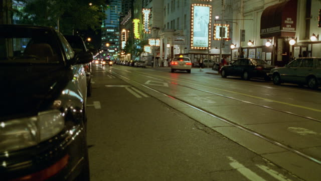 MEDIUM ANGLE TRACKING SHOT OF GRAY LIMO PASSING TO RIGHT ON NARROW CITY STREET WITH MANY NEON SIGNS.