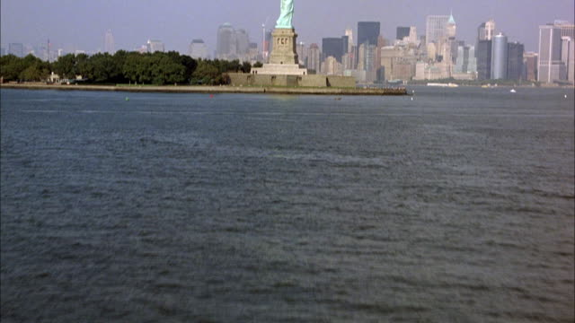 AERIAL OF STATUE OF LIBERTY AND SURROUNDING WATER. SEE NEW YORK CITY SKYLINE IN BACKGROUND. SMOGGY.