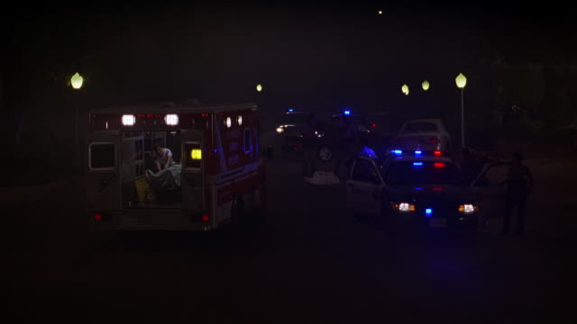 HAND HELD OF EMERGENCY OR CRIME SCENE. POLICE CARS AND AMBULANCE ALL WITH FLASHING BIZBAR LIGHTS. PERSON ON STRETCHER VISIBLE IN BACK OF AMBULANCE. RESIDENTIAL AREA OR NEIGHBORHOOD.