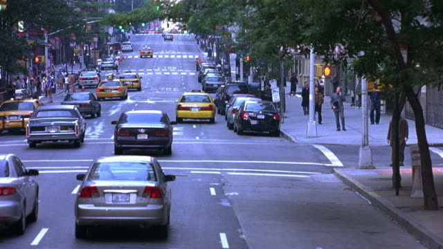 MEDIUM ANGLE, DRIVING POV STRAIGHT FORWARD OF CROWDED NEW YORK, NYC STREETS. CARS, TAXIS.  WOMAN EXITING TAXI.