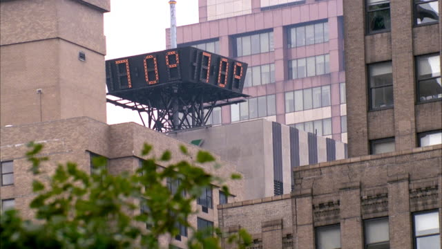 MEDIUM ANGLE OF LARGE SIGN OF ELECTRONIC THERMOMETER AND CLOCK MOUNTED ON TOP OF BUILDING IN DOWNTOWN AREA. SEE SIGN FLASH BETWEEN TIME 10:47 AND TEMPERATURE OF 70* AND 21C. SEE LARGE OFFICE BUILDINGS IN BACKGROUND.