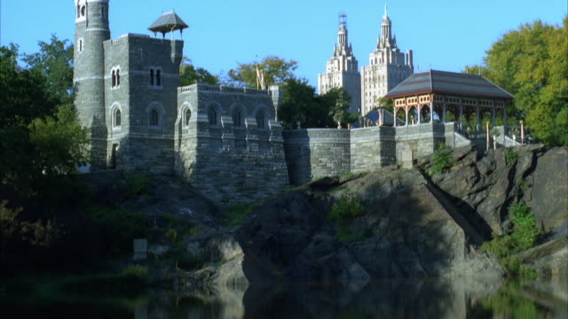 PAN UP OF BELVEDERE CASTLE ON  ROCK CLIFF BY LAKE IN CENTRAL PARK. SMALL AMERICAN FLAG FLAPS ON TOP OF SPIRE, DOCK OR WALKWAY VISIBLE AT RIGHT. STONE BUILDING. PANS DOWN, THEN BACK UP AGAIN.
