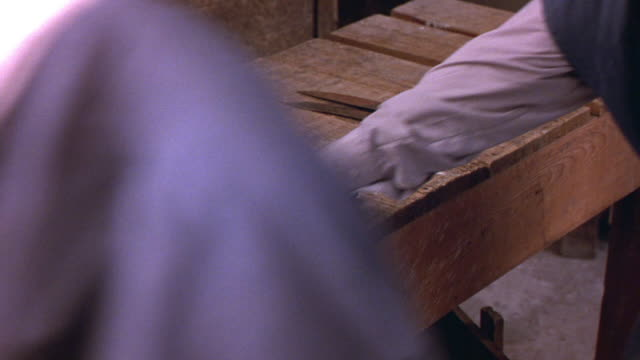 CLOSE ANGLE OF WOODEN TABLE WITH SEVERAL KNIVES ON IT. MEN WALK BY ONE BY ONE AND PICK UP KNIVES THEN CROSS IN FRONT OF CAMERA. MAN PULLS WOODEN BOX FROM UNDER TABLE.