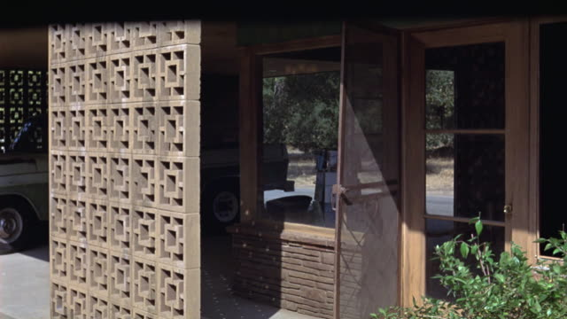 MEDIUM ANGLE OF LOWER CLASS HOTEL OR MOTEL FRONT DOOR TO LOBBY. VINTAGE PICKUP TRUCK PARKED. RUSTIC BUILDING. MATCHING.