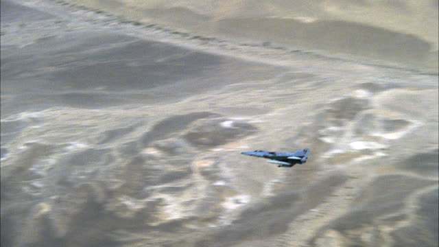 PAN RIGHT TO LEFT OF KFIR MILITARY JET FLYING ACROSS SCREEN FROM RIGHT TO LEFT, DESERT LANDSCAPE VISIBLE IN BACKGROUND. MIDDLE EAST.