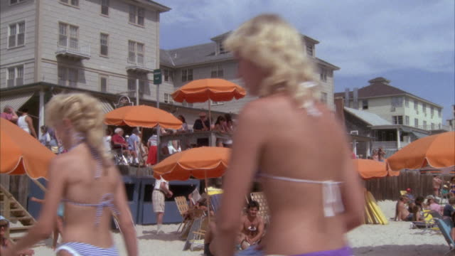 MEDIUM ANGLE OF CROWD IN BATHING SUITS WALKING BY BEACH, SEE ORANGE PARASOLS AND SUNBATHERS BELOW. SOME PEOPLE WALK TO LEFT TOWARD BOARDWALK. SEE THREE STORY CONDOMINIUMS IN LEFT BACKGROUND.