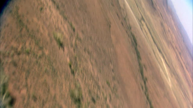 AERIAL OF DESERT OR ARID LAND. SEE SCATTERED SHRUBS AND PLANTS. SEE MOUNTAINS, HILLS, AND BLUE SKY IN BACKGROUND. POV TURNS IN VARIOUS DIRECTIONS.