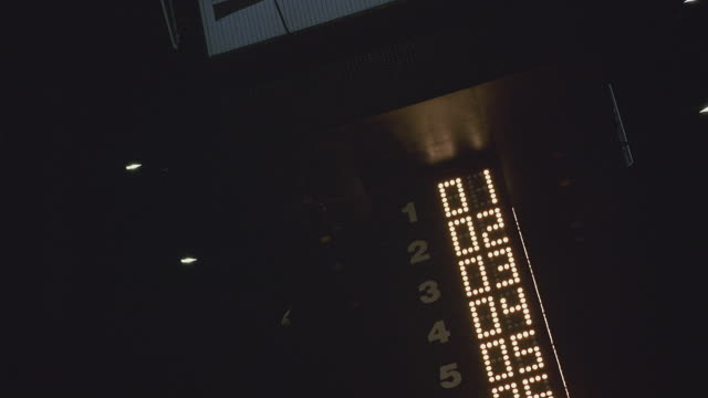 MEDIUM ANGLE OF RACETRACK, TOWER, LIGHTED SCOREBOARD WHICH SHOWS RACE CARS' POSITIONS IN THE RACE BY NUMBER. RACING.