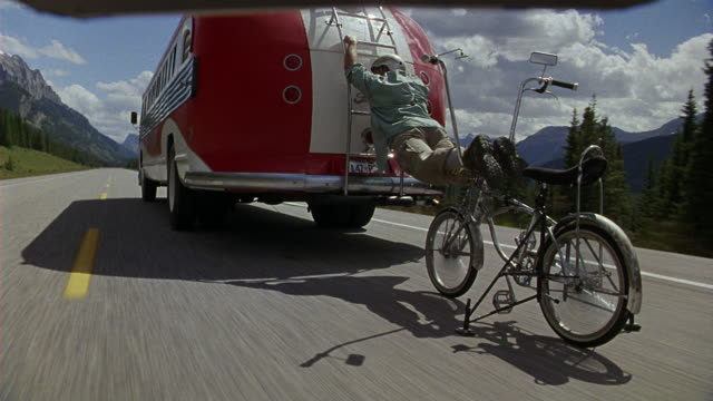 TRACKING SHOT CLOSE ANGLE  OF STUNT DOUBLE CLIMBING FROM BICYCLE ONTO BACK OF MOVING RED AND WHITE FLXIBLE BUS. BICYCLE FALLS ONTO HIGHWAY. MAN CLIMBS ONTO LADDER ON BACK OF BUS AS IT SPEEDS DOWN TWO LANE HIGHWAY.